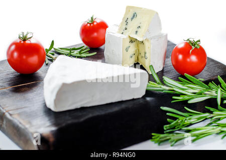 Assorted cheeses on wooden board. Camembert, cheese with blue mildew, mozzarella with tomatoes and rosemary - Stock Photo