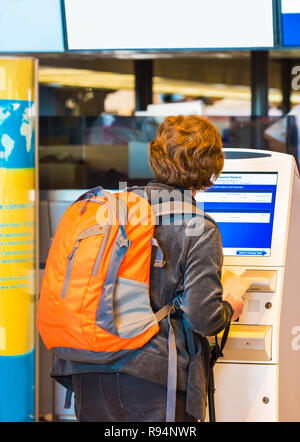 TOKYO, JAPAN - NOVEMBER 7, 2017: Woman with orange backpack at the airport check-in counter. Back view. With selective focus - Stock Photo