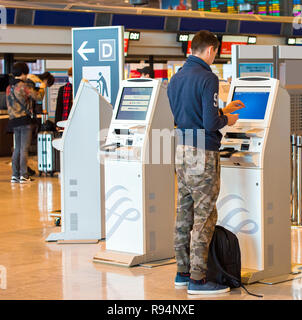 TOKYO, JAPAN - NOVEMBER 7, 2017: A man near the check-in counter at the airport. Back view. With selective focus - Stock Photo