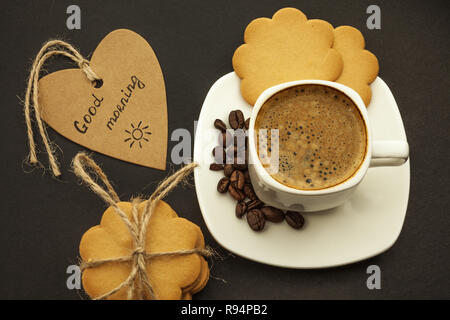 Black coffee with coffee beans and cookies on a dark background. Breakfast, top view. - Stock Photo