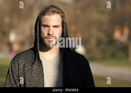 handsome bearded man or serious hooded guy with beard sunny outdoor on blurred background - Stock Photo