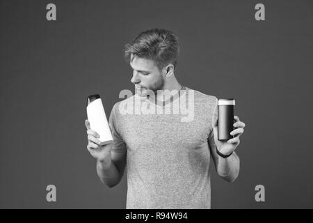 Man on thoughtful face chooses shampoo, violet background. Guy with bristle holds two bottles with shampoo, copy space. Man hesitates while making alternative decision. Hair care and shampoo concept. - Stock Photo