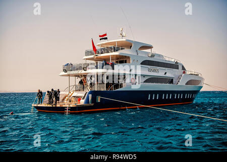 Hurghada, Egypt - February 24, 2017: white ship or yacht, modern motor boat and group of people, scuba divers, in wetsuits, snorkels in blue sea on summer day on clear sky. Snorkeling activity - Stock Photo