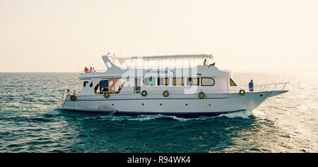 Hurghada, Egypt - February 24, 2017: tourist white ship or yacht, modern motor boat floating on blue sea water on sunny day on clear sky background. Travelling and adventure - Stock Photo