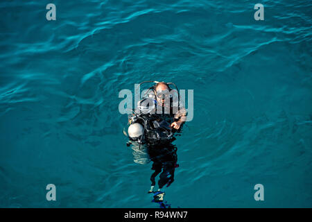 Hurghada, Egypt - February 24, 2017: underwater, snorkeling diver, man in wetsuit with snorkel, scuba, aqualung, mask swimming in sea or ocean on sunny day on blue background. Idyllic summer vacation - Stock Photo