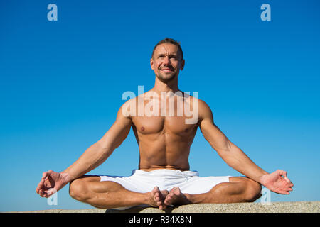 Yoga helps find balance and unite with nature. Yoga practice helps find harmony and balance. Man practicing yoga blue sky background. Reached peace of mind. Meditation and yoga concept. - Stock Photo