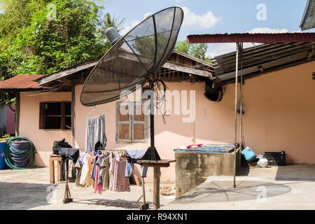Large freestanding satellite dish outside a house at the Whisky village. Ban Xiang Hai, Luang Prabang, Louangphabang province, Laos, southeast Asia - Stock Photo