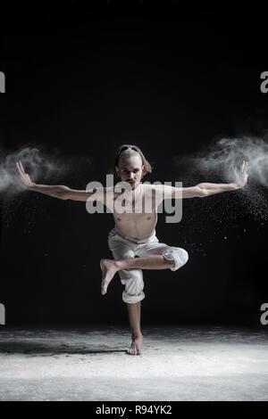 Sporty young man practicing yoga, doing balance exercise on leg, balancing posture - Stock Photo