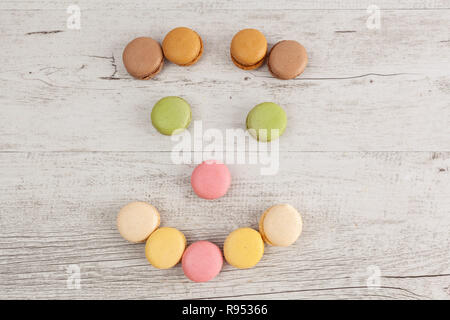 Smiling face with eyebrows made from colorful macarons on wooden table with copy space - Stock Photo
