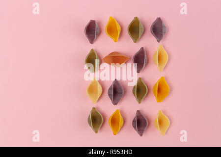 Colorful Conchiglie Rigate pasta on pink background with copy space - Stock Photo