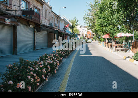 Sunny morning in Goreme - street with flowers and closed shops and empty street cafes - Stock Photo