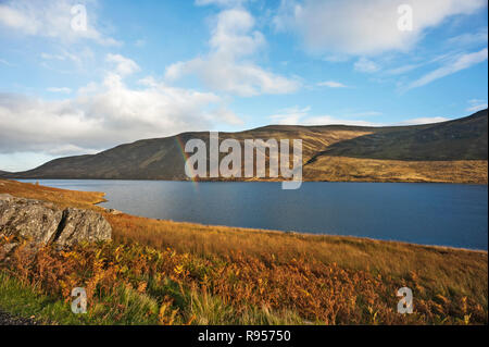 Partial rainbow over Loch Lee, Glen Esk, Angus, Scotland, UK, in foreground  on sunny day with loch side hills and bright cloudy blue sky in background. - Stock Photo