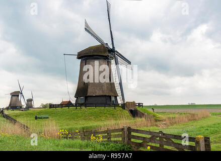 The Schermerhorn Museum Mill in a row of three windmills on a blustery cloudy day at Schermerhorn, North Holland, The Netherlands - Stock Photo