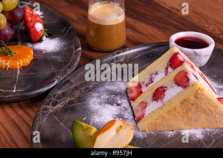 Strawberry cake, coffee and fruit plate on wooden table - Stock Photo
