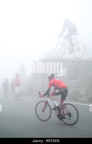 Tourists watching the statue for Tour de France cyclist Octave Lapize at the Col du Tourmalet in thick mist in the Pyrenees, France - Stock Photo