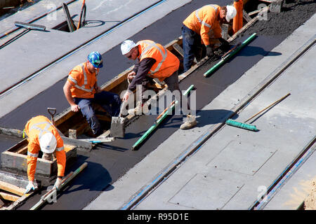 Concrete workers pouring concrete in Scott Street to build the Newcastle Light Rail (Tram) service for the city. - Stock Photo