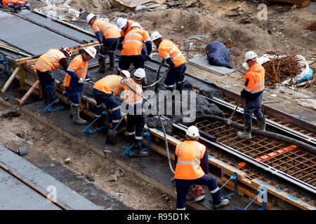 Construction workers building a light rail track for trams in the Newcastle CBD, Australia. - Stock Photo