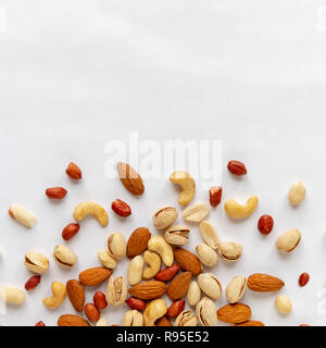 Assorted roasted and raw nuts scattered on white with almonds, peanuts, groundnuts, pistachios and cashews viewed in a flat lay still life from above  - Stock Photo