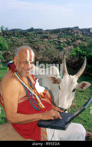 Sanskrit scholar or sadhu with computer and cow melkote, karnataka, india NO MR - Stock Photo