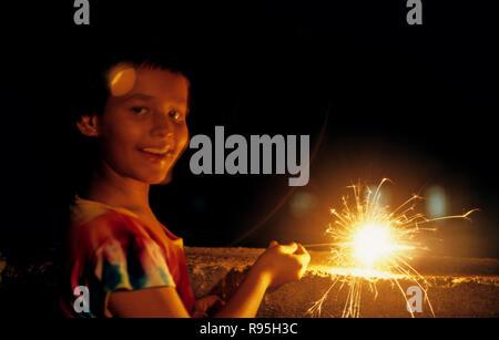 Girl burning fire cracker on Diwali Festival of Lights Bombay Mumbai Maharashtra India - Stock Photo