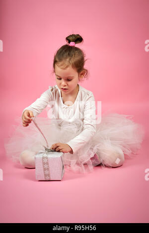Cute little girl in white tulle skirt opens a gift on a pink background - Stock Photo