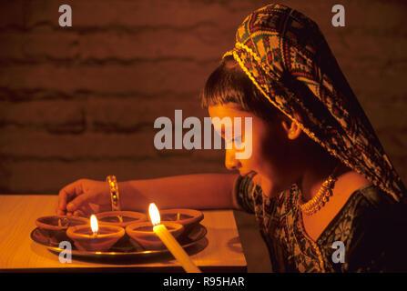 Girl lighting oil lamps Diwali Deepawali Festival of lights Bombay Mumbai Maharashtra India - Stock Photo