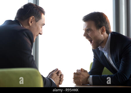 Screaming businesspeople sitting face to face staring to each ot - Stock Photo