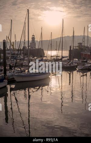 The harbour and marina at Scarborough.  The boats are silhouetted and the masts and the morning sun are reflected in the still water. - Stock Photo