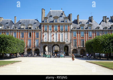 PARIS, FRANCE - JULY 6, 2018: Place des Vosges with ancient buildings and some people at midday in a sunny summer day, clear blue sky in Paris
