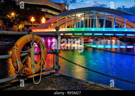 A lifebelt by the Singapore River near Boat Quay, Singapore; lit up Elgin Bridge in the background - Stock Photo
