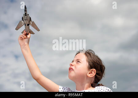 Young girl playing with Russian fighter jet model - Stock Photo