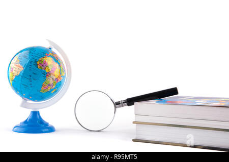 Globe witn magnifying glass on book - Stock Photo