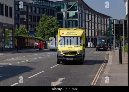 NHS London UK ambulance emergency SOS call National Health Service paramedic crew on board responding 999 call driving & speeding blue flashing light - Stock Photo