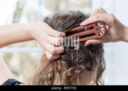 Closeup behind portrait of female back, young brunette woman making hair with three prong wooden fork, Chinese, Asian stick, hairpin, standing in home - Stock Photo