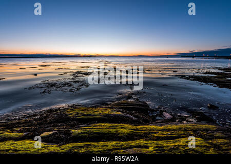Twilight, dusk in Rimouski, Quebec, Saint Lawrence river, Gaspesie, Canada with rocks, boulders, rocky beach, turquoise water, sun reflection seaweed  - Stock Photo