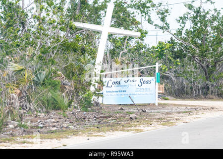 Big Pine Key, USA - May 1, 2018: Lord of the seas lutheran church on Key Deer boulevard with white cross, sign for service hours, broken, damage, dama - Stock Photo