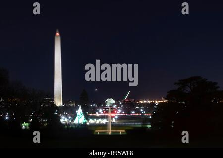 View of the Washington Monument and National Mall from the South Lawn of the White House decorated for Christmas and lighted at night December 12, 2018 in Washington, DC. The light streaks are commercial airplanes taking off from Reagan National Airport on the Potomac River. - Stock Photo