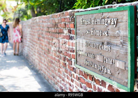 Key West, USA - May 1, 2018: Sign for Ernest Hemingway Home, residence, museum with no credit cars, cash only, hours information, on red brick wall at - Stock Photo