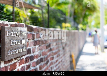 Key West, USA - May 1, 2018: Sign for Ernest Hemingway Home, residence, museum, direction to entrance at corner turn left information on red brick wal - Stock Photo