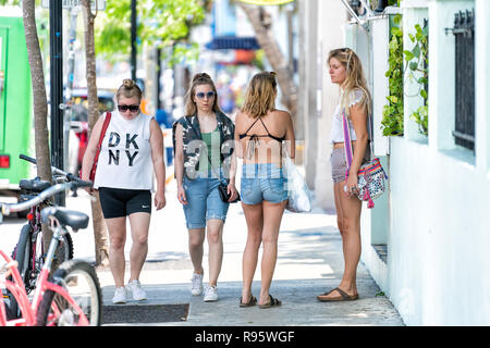Key West, USA - May 1, 2018: People, young women, girls standing in Florida city travel, sunny hot day, street, parking, bicycles, hotel entrance, tal - Stock Photo