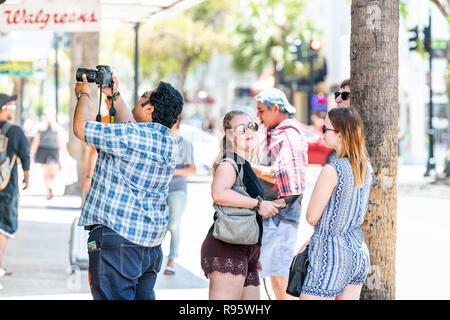 Key West, USA - May 1, 2018: Group of young people, tourists, women standing on sidewalk of Duval street road in summer, restaurant entrance, taking p - Stock Photo