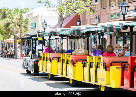 Key West, USA - May 1, 2018: Back of people, tourists riding yellow black conch train guided tour bus, trolley with guide driver in Florida keys city  - Stock Photo