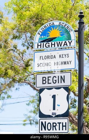 Key West, USA - May 1, 2018: Florida scenic highway, keys begin US1, US one, 1, North route, road street, overseas hwy, freeway sign with art painting - Stock Photo