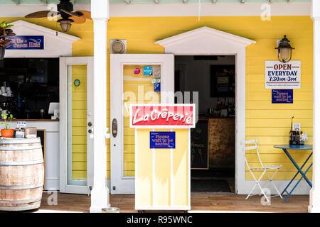 Key West, USA - May 1, 2018: La Creperie in Florida keys city on street, sidewalk with building, restaurant, cafe entrance, sign for open hours, pleas - Stock Photo