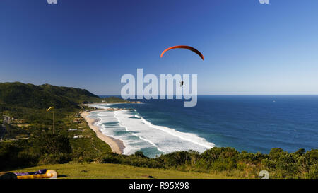 Paraglinding from the hill of Mole beach over the sea and mountains. Florianópolis, Santa Catarina state, South America, Brazil. - Stock Photo