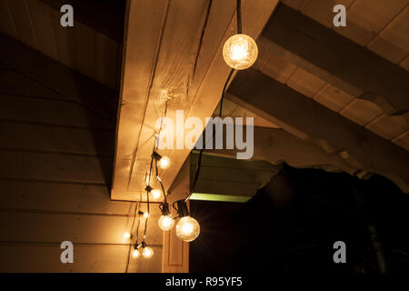 Decorative outdoor string lights hanging on tree in the garden at night time - Stock Photo