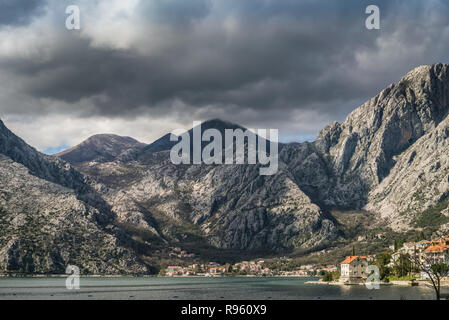 Red tiled houses on the Boka Bay shore in front of the stunning mountain landscape in the Bay of Kotor, Montenegro - Stock Photo