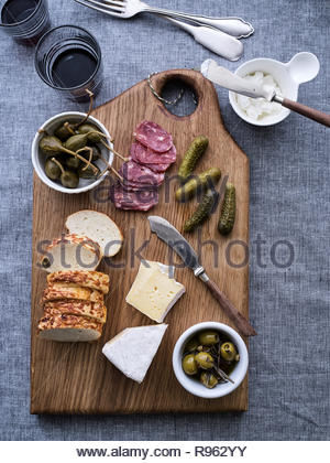 Charcuterie concept. Overhead view of cured meats, sausage, bread, pickles different types of cheeses, and wine glass. Textile background. - Stock Photo