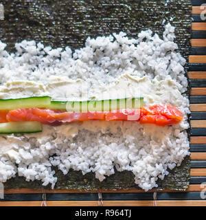 Making Sushi Rolls: Salmon Fish Strips, Cucumber Sticks, Cream Cheese, Rice and Nori Seaweed Sheet on a Bamboo Mat - Stock Photo