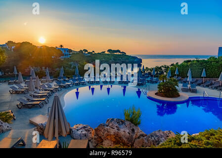 Beautiful sunrise above swimming pool resort on the coast of Mallorca island, in Cala d`Or region, Spain - Stock Photo